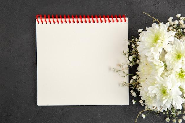 Vue de dessus bloc-notes en spirale bouquet de fleurs sur fond sombre