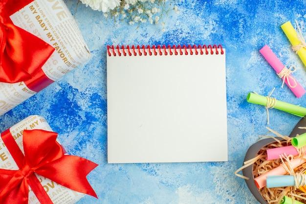 Vue de dessus bloc-notes spirale cadeaux défilement papiers de souhaits sur fond bleu