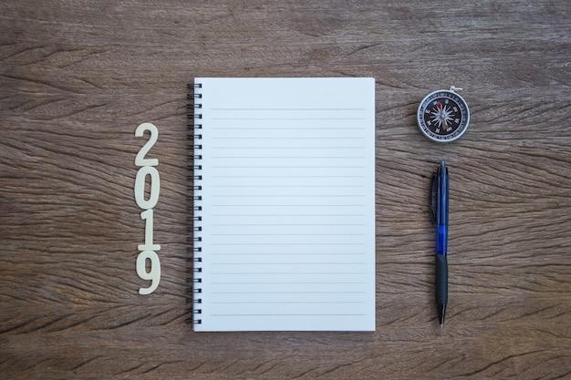 Vue de dessus, bloc-notes, stylo et compas portant le numéro 2019 du bois coupé.
