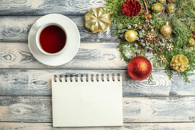 Vue de dessus un bloc-notes une tasse de branches de sapin de thé sur fond de bois