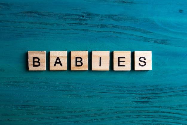 Vue de dessus des blocs de l'alphabet avec des lettres sur fond en bois bleu. inscription bébés.