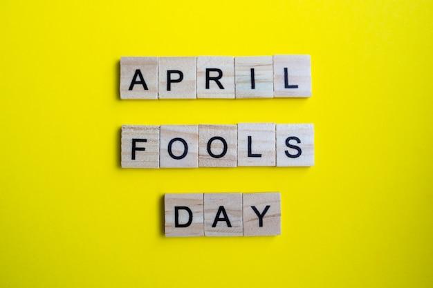Vue de dessus des blocs de l'alphabet avec des lettres sur fond jaune vif. poisson d'avril - lettrage.