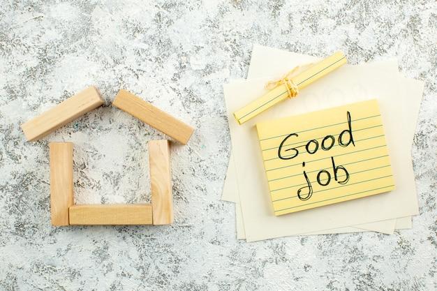 Vue de dessus des blocs de bois en forme de maison bon travail écrit sur pense-bête sur fond gris blanc