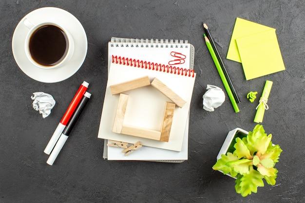 Vue de dessus blocs de bois en forme de maison cahiers à spirale marqueurs rouges et noirs crayons verts et noirs tasse de thé notes autocollantes sur noir