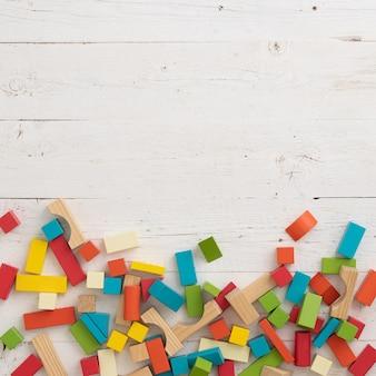 Vue de dessus des blocs de jouets en bois colorés sur fond de table en bois blanc