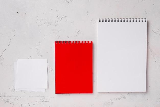 Vue de dessus des blocs-notes organisés sur le bureau avec des notes autocollantes