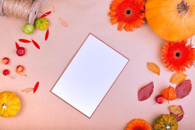 Vue de dessus de boîte-cadeau artisanale, fleurs jaunes et orange et citrouilles sur fond rose. carte de voeux vierge pour la conception de travaux créatifs. mise à plat