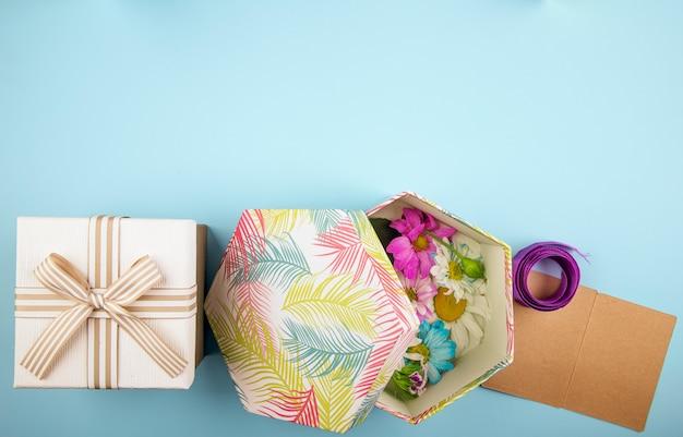 Vue de dessus d'une boîte cadeau attachée avec un arc et une boîte cadeau remplie de fleurs de chrysanthème colorées avec marguerite et ruban violet avec petite carte postale sur fond bleu