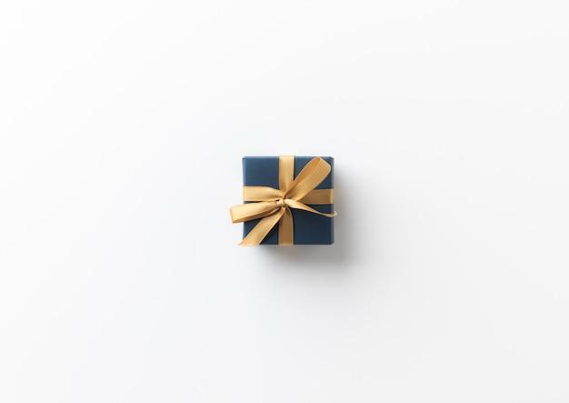 Vue de dessus boîte cadeau cadeau bleu avec ruban d'or sur la table blanche