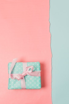 Vue de dessus de la boîte cadeau enveloppée sur une surface bicolore