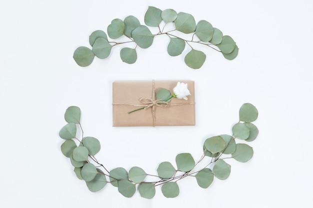 Vue de dessus d'une boîte cadeau kraft vintage avec cadre de fleurs sur un bureau lumineux, plat poser. carte de voeux