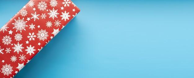 Vue de dessus de boîte cadeau de noël rouge isolée sur fond bleu. espace de copie.