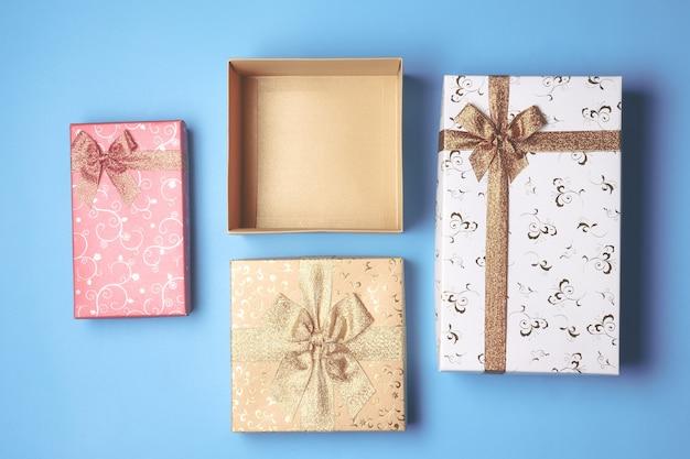 Vue de dessus de boîte-cadeau ouverte et présente sur fond bleu.