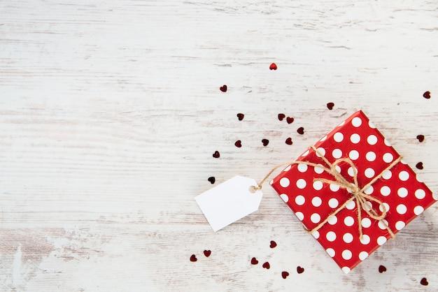 Vue de dessus d'une boîte de cadeau en pointillé rouge sur bois blanc, fond. note vide