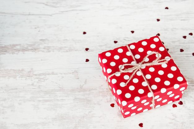 Vue de dessus d'une boîte de cadeau en pointillé rouge sur bois blanc, fond.
