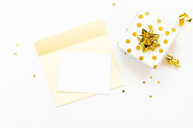 Vue de dessus de la boîte-cadeau en pointillés dorés et de l'enveloppe ouverte avec une carte vide sur fond blanc. espace de copie, maquette.