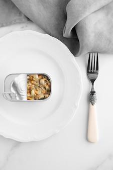 Vue de dessus boîte de conserve avec de la nourriture sur une assiette avec une fourchette