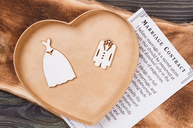 Vue de dessus boîte en forme de coeur et contrat de mariage. accessoires de mariage à plat.