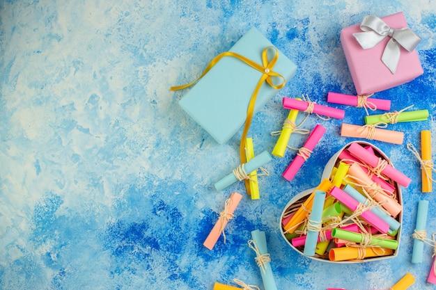 Vue de dessus boîte en forme de coeur avec défilement papiers de souhaits cadeaux sur fond bleu copie lieu