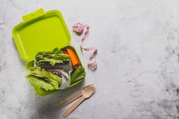Vue de dessus de la boîte à lunch avec un ruban à mesurer et couverts