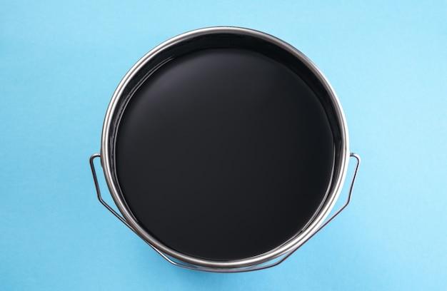 Vue de dessus de la boîte de peinture de couleur noire sjiny sur fond bleu avec espace de copie