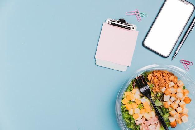 Vue de dessus boîte à salade de travail avec téléphone vierge et copie-espace