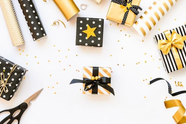Vue de dessus des boîtes-cadeaux et des matériaux d'emballage en noir, blanc et or