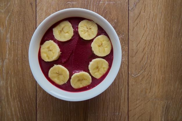 Vue de dessus bol avec bananes et granola.
