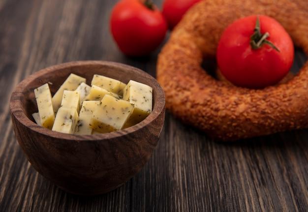 Vue de dessus d'un bol en bois avec des tranches de fromage hachées avec des tomates sur un fond en bois