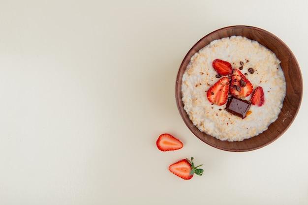 Vue de dessus d'un bol de flocons d'avoine avec du chocolat au fromage cottage et des fraises sur le côté droit et une surface blanche avec copie espace