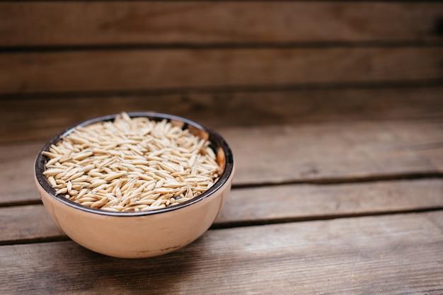 Vue de dessus un bol de grains d'avoine sur un fond en bois, aliments naturels