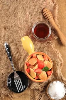 Vue de dessus bol jaune avec poignée pleine de petites crêpes ou populaire comme collation virale aux crêpes aux céréales