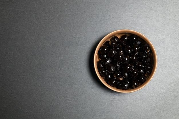 Vue de dessus: bol d'olives noires sur pierre ardoise rustique noire