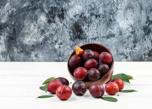 Vue de dessus un bol de prunes et de fraises sur napperon en osier sur planche de bois blanc et surface en marbre bleu foncé.