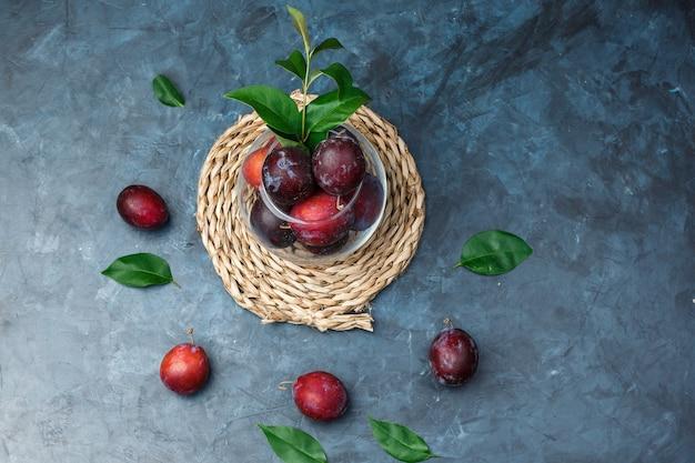 Vue de dessus un bol de prunes sur napperon en osier sur une surface en marbre bleu foncé. horizontal