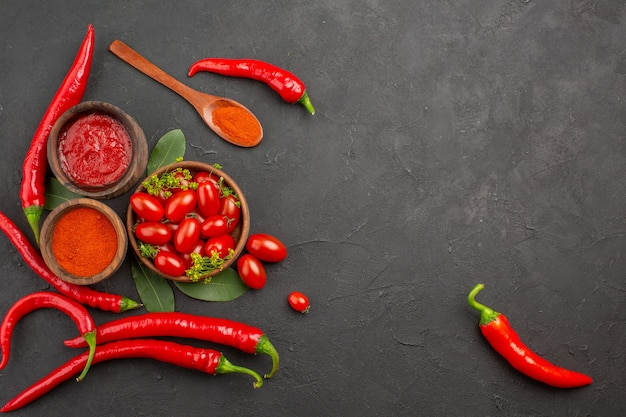 Vue de dessus un bol de tomates cerises piments rouges chauds une cuillère en bois feuilles de laurier et bols de ketchup et de poudre de piment sur fond noir