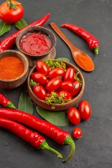 Vue de dessus un bol de tomates cerises poivrons rouges chauds laurier laisse une cuillère en bois bols de ketchup et de poudre de piment rouge et de tomate sur le côté gauche du sol noir