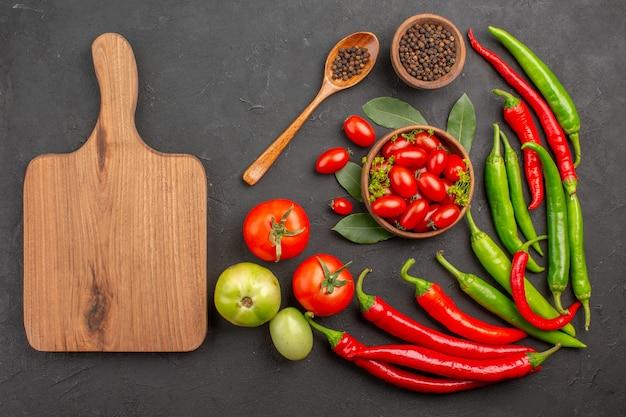 Vue de dessus un bol de tomates cerises poivrons rouges chauds poivre noir dans une cuillère en bois un bol de poivre noir et une planche à découper sur fond noir