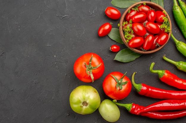 Vue de dessus un bol de tomates cerises poivrons rouges et verts chauds et tomates sur fond noir