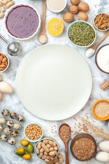 Vue de dessus bols en assiette blanche avec amandes graines de maïs arachides grains de blé graines de sésame confiture oeufs noix oeufs de caille