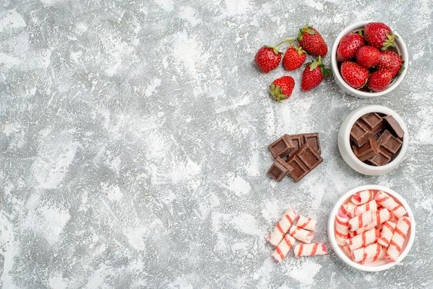 Vue de dessus des bols avec des bonbons chocolats fraises et quelques bonbons chocolats fraises sur le côté droit du sol gris-blanc