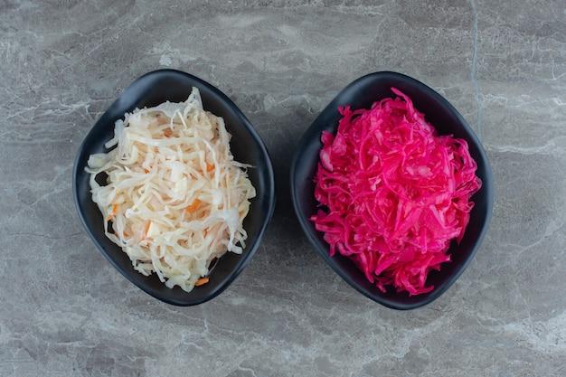 Vue de dessus des bols de choucroute blancs et roses.
