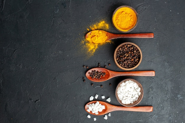 Vue de dessus bols avec cuillères en bois de sel sae poivre noir curcuma sur espace libre de surface noire