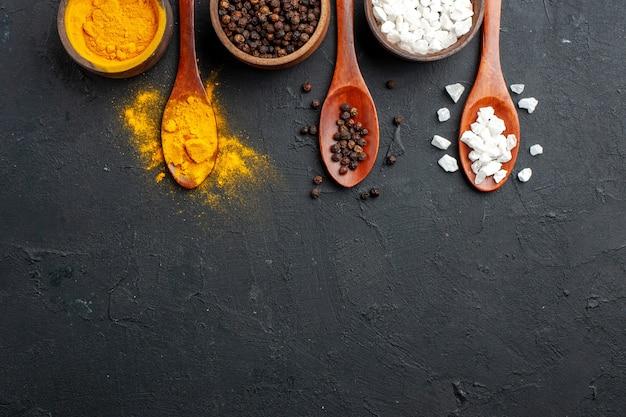 Vue de dessus bols avec cuillères en bois de sel sae poivre noir curcuma sur surface noire copie place