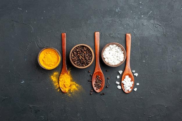 Vue de dessus des bols avec cuillères en bois de sel sae poivre noir curcuma sur surface noire avec place de copie