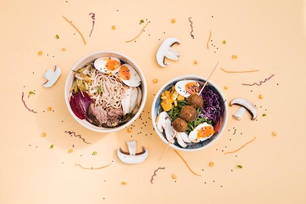 Vue de dessus de bols de cuisine asiatique traditionnelle décorés avec des champignons et des graines de sésame sur un fond coloré