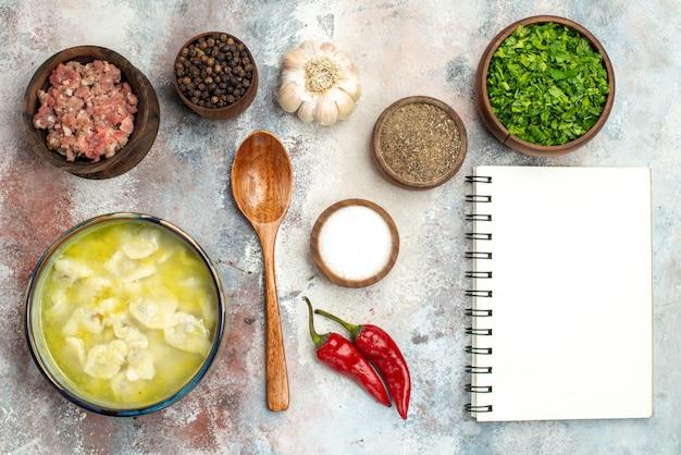 Vue de dessus bols de dushbara avec différentes épices verts viande cuillère en bois un cahier sur la photo de nourriture de surface nue