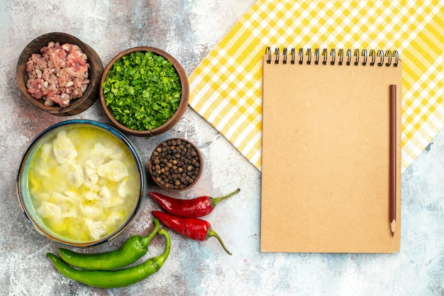 Vue de dessus bols de dushbara avec des légumes verts de viande poivre noir piments forts bloc-notes de serviette de cuisine avec un crayon sur la surface nue
