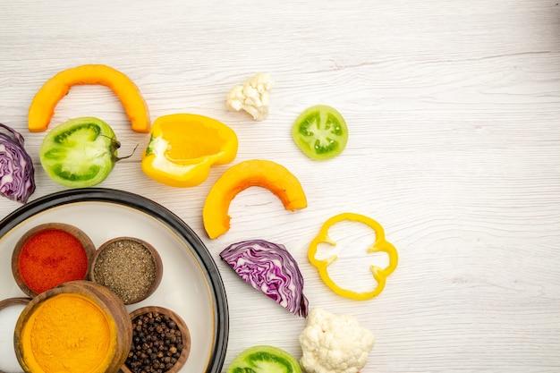 Vue de dessus bols avec épices curcuma poivre noir sel poivre rouge poudre de légumes coupés sur une surface blanche avec espace libre
