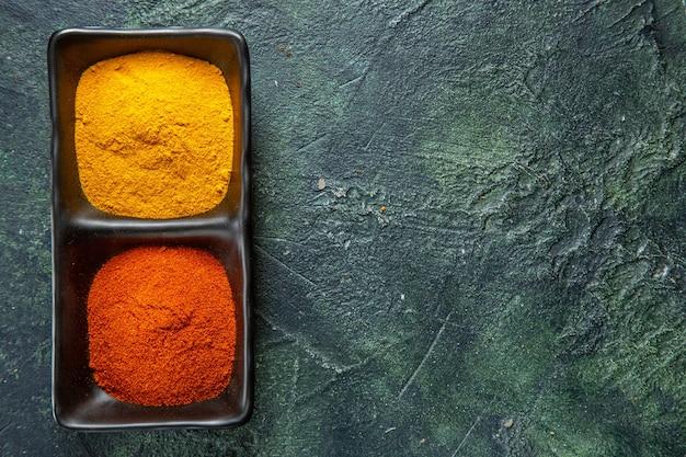 Vue de dessus des bols d'épices remplis de poivron rouge et de gingembre jaune sur le côté droit sur fond de mélange de couleurs avec de l'espace libre